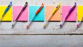 Tabela de madeira branca retro com notas pegajosas coloridas vazias Foto de Stock Royalty Free