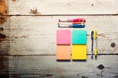 Tabela de madeira branca retro com notas pegajosas coloridas vazias Fotos de Stock Royalty Free
