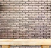 Tabela de madeira clara vazia e parede de tijolo vermelho do borrão no fundo, Moc imagens de stock