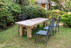 Tabela de madeira com as cadeiras no jardim obscuro Imagem de Stock Royalty Free