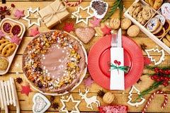 Tabela de madeira com as decorações deliciosas do bolo do Natal e as cookies diferentes imagem de stock