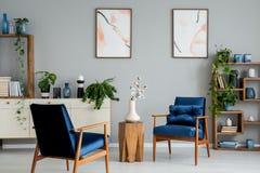 Tabela de madeira com as flores entre poltronas azuis no interior cinzento com cartazes e plantas fotografia de stock royalty free