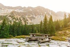 Tabela de madeira com bancos em uma plataforma de pedra entre as montanhas imagens de stock