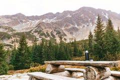 Tabela de madeira com bancos em uma plataforma de pedra entre as montanhas Garrafa térmica com bebida quente foto de stock