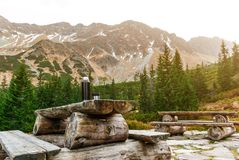Tabela de madeira com bancos em uma plataforma de pedra entre as montanhas Garrafa térmica com bebida quente fotografia de stock