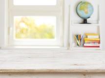 Tabela de madeira com fundo borrado da sala e da janela das crianças imagem de stock