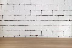 Tabela de madeira com fundo branco do tijolo Fotos de Stock