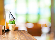 Tabela de madeira com lâmpada e moldura para retrato em vagabundos borrados do café do jardim Fotos de Stock Royalty Free