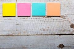 Tabela de madeira com notas pegajosas coloridas vazias Fotografia de Stock Royalty Free