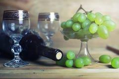 Tabela de madeira com o livro e a uva da garrafa de vinho Fotografia de Stock
