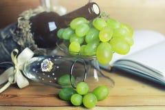 Tabela de madeira com o livro e a uva da garrafa de vinho Fotografia de Stock Royalty Free