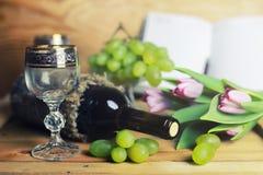 Tabela de madeira com o livro e a uva da garrafa de vinho Fotos de Stock Royalty Free