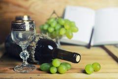 Tabela de madeira com o livro e a uva da garrafa de vinho Foto de Stock
