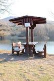 Tabela de madeira com os bancos ao lado da praia para o resto após o banho no lago fotos de stock