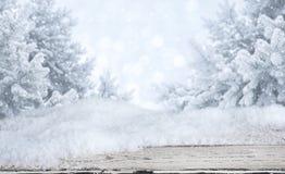Tabela de madeira com os montes de neve sobre o fundo abstrato borrado da paisagem do inverno fotos de stock