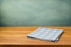 Tabela de madeira com toalha de mesa na parede do azul do grunge Fotos de Stock