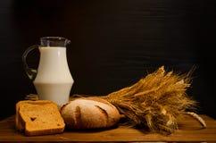 Tabela de madeira com um jarro de leite, de pão de centeio e de uma polia, um fundo preto Imagem de Stock