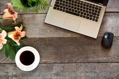 Tabela de madeira da mesa do escritório com portátil, flor e copo do café preto Vista superior com espaço da cópia Imagem de Stock