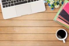Tabela de madeira da mesa de escritório com caderno, flor, xícara de café e g foto de stock