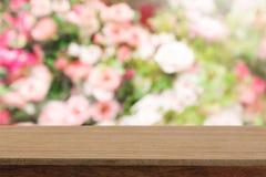 Tabela de madeira da perspectiva na parte superior sobre as rosas b natural pastel do borrão Foto de Stock
