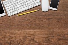 Tabela de madeira do escritório com lápis amarelo, tabuleta, teclado, rato Fotografia de Stock