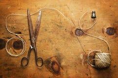A tabela de madeira do vintage com dedal, linha e scissor Foto de Stock