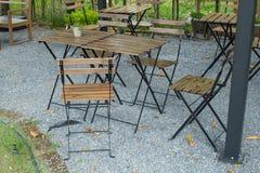 Tabela de madeira e cadeiras que assentam no jardim foto de stock