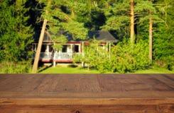 a tabela de madeira em árvores de floresta verdes dianteiras ajardina o fundo para a exposição e a apresentação do produto Foto de Stock