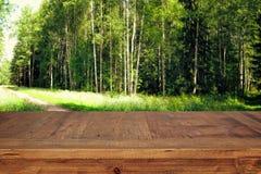 a tabela de madeira em árvores de floresta verdes dianteiras ajardina o fundo para a exposição e a apresentação do produto Fotos de Stock