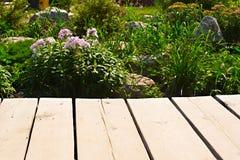 A tabela de madeira em um fundo do jardim floresce Imagem de Stock Royalty Free