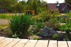 A tabela de madeira em um fundo do jardim floresce Imagens de Stock Royalty Free