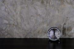 Tabela de madeira escura com o despertador na parede concreta cinzenta do estilo do sótão fotografia de stock royalty free