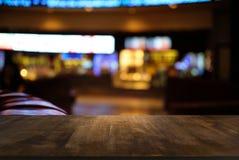 A tabela de madeira escura vazia na frente do sumário borrou o backg do bokeh Foto de Stock