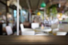 A tabela de madeira escura vazia na frente do sumário borrou o fundo do bokeh do restaurante fotos de stock