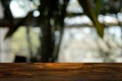 A tabela de madeira escura vazia na frente do sumário borrou o fundo do bokeh do restaurante fotografia de stock
