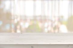 Tabela de madeira na frente do fundo transparente borrado da cortina de janela Imagem de Stock Royalty Free