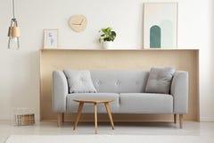 Tabela de madeira na frente do sofá cinzento no interio simples da sala de visitas imagens de stock