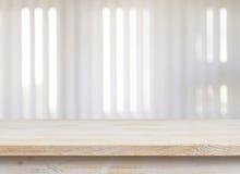 Tabela de madeira na janela defocuced com fundo do jalousie imagens de stock