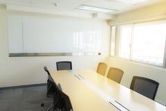 Tabela de madeira na luz solar da placa branca da sala de reunião da janela Fotografia de Stock