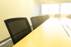 Tabela de madeira na luz solar da placa branca da sala de reunião da janela Fotos de Stock