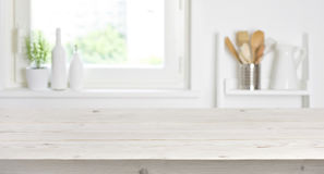 Tabela de madeira no fundo borrado da janela e das prateleiras da cozinha imagens de stock