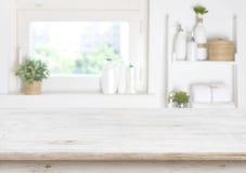 Tabela de madeira no fundo borrado da janela e das prateleiras do banheiro imagens de stock
