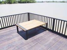 Tabela de madeira no terraço de madeira perto do rio imagem de stock royalty free