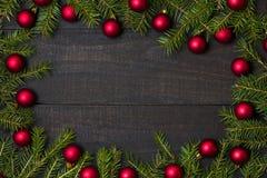 Tabela de madeira rústica escura flatlay - fundo do Natal com a decoração do ornamento da bola e quadro vermelhos do ramo do abet imagem de stock royalty free