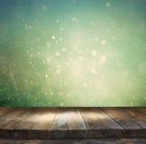 A tabela de madeira rústica na frente da prata do brilho, do azul, e do bokeh do ouro ilumina-se Imagem de Stock Royalty Free