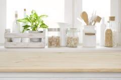 Tabela de madeira sobre o peitoril borrado da janela da cozinha para a exposição do produto fotografia de stock
