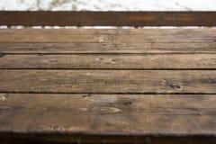 Tabela de madeira vazia com bokeh da neve para uma textura do piquenique da restauração ou do alimento imagem de stock
