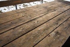 Tabela de madeira vazia com bokeh da neve para uma textura do piquenique da restauração ou do alimento fotografia de stock