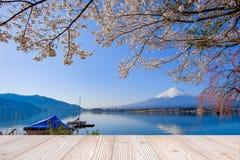 A tabela de madeira vazia com montanha de Fuji e o fundo cor-de-rosa bonito da flor da flor de cerejeira na estação de mola, zomb fotos de stock royalty free