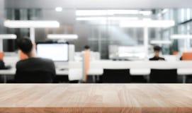 Tabela de madeira vazia com o trabalhador do borrão que trabalha no escritório imagens de stock